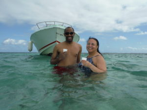 Ian and Tonya standing on a sand bar in Josephine's bath while enjoying a Planteur Punch.
