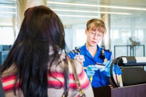 A TSA officer authenticates a traveler's credentials.  Photo courtesy of TSA.