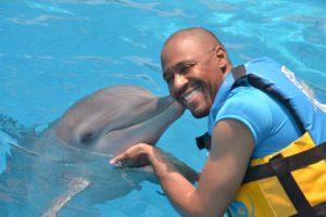 World Footprints co-founder, Ian Fitzpatrick, enjoys a kiss from Dori the dolphin.
