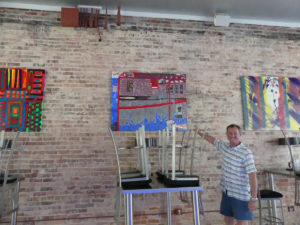 Steven Hill shows his painting in tap room at Mother Earth Brewery. Photo: Kathleen Walls