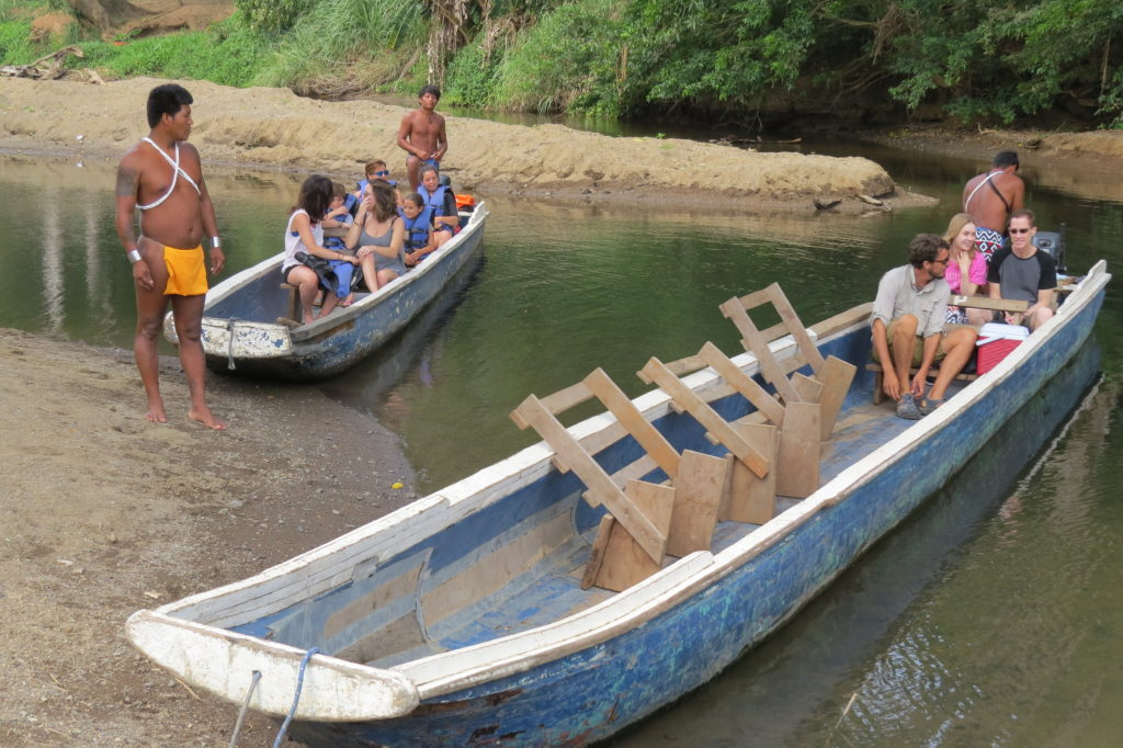 Family on a wooden longboat in Panama. Photo: Chez