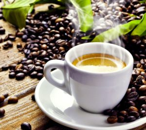Cup of coffee from Costa Rica surrounded by beans and green leaves.