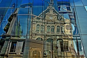 A historic cathedral reflects off of a modern glass building in Lyon, France.