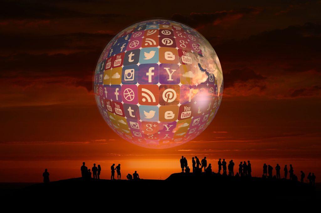 Globe of social media above travelers.