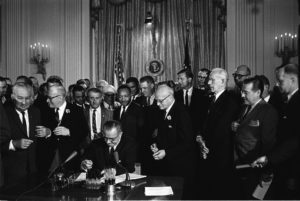 President Lyndon Johnson signs the 1968 Civil Rights Act into law. He is surrounded by Civil Rights activists including Dr. Martin Luther King.