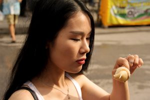 Asian woman eating and walking