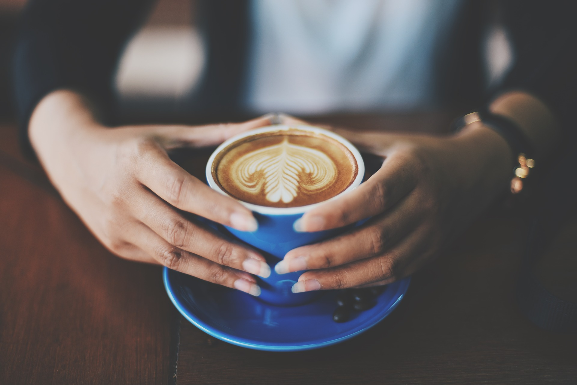 Customer embracing coffee cup in cafe symbolizes inclusion.