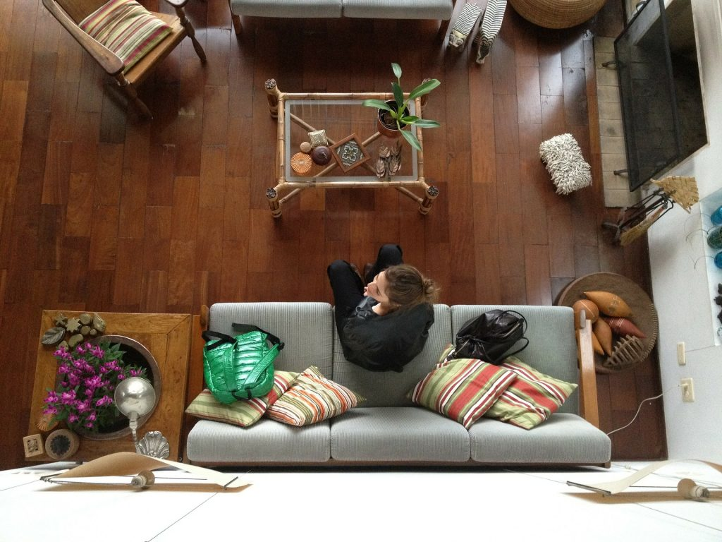 Travel the world by housesitting. Photo of a girl sitting alone in a large house.