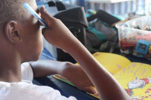 Teaching is a popular voluntourism activity. Here we see a child doing homework. Photo: Breana Johnson