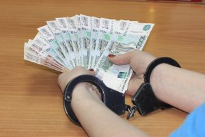 Handcuffed hands passing money to police as bribe.