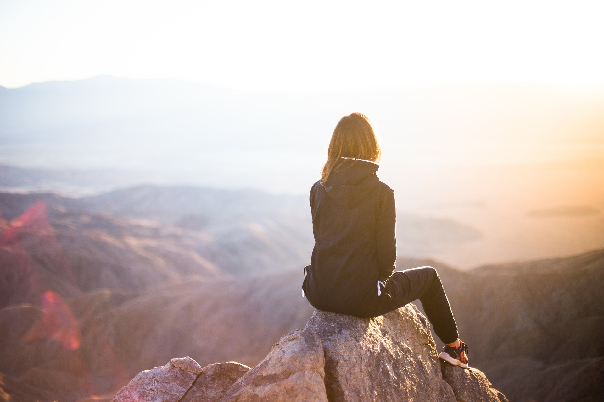 Woman reflecting on the side of a mountain.