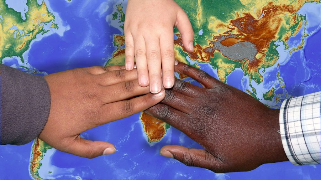 Hands of many colors on the world