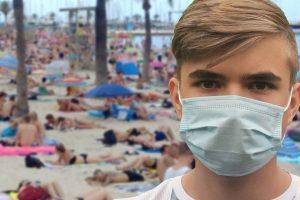 Single mask wearer on crowded beach