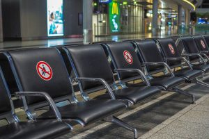 Airport seats in an empty airport. Every other seat is blocked off for social distancing because of COVID