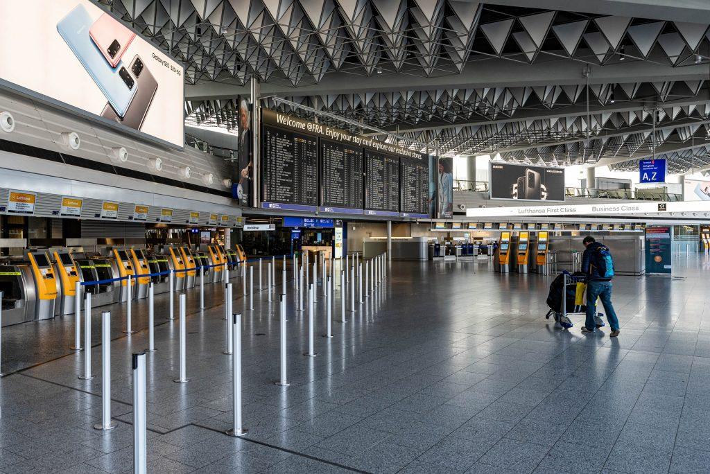 Safe Travel - empty airport showing one passenger traveling to his gate. coronavirus image