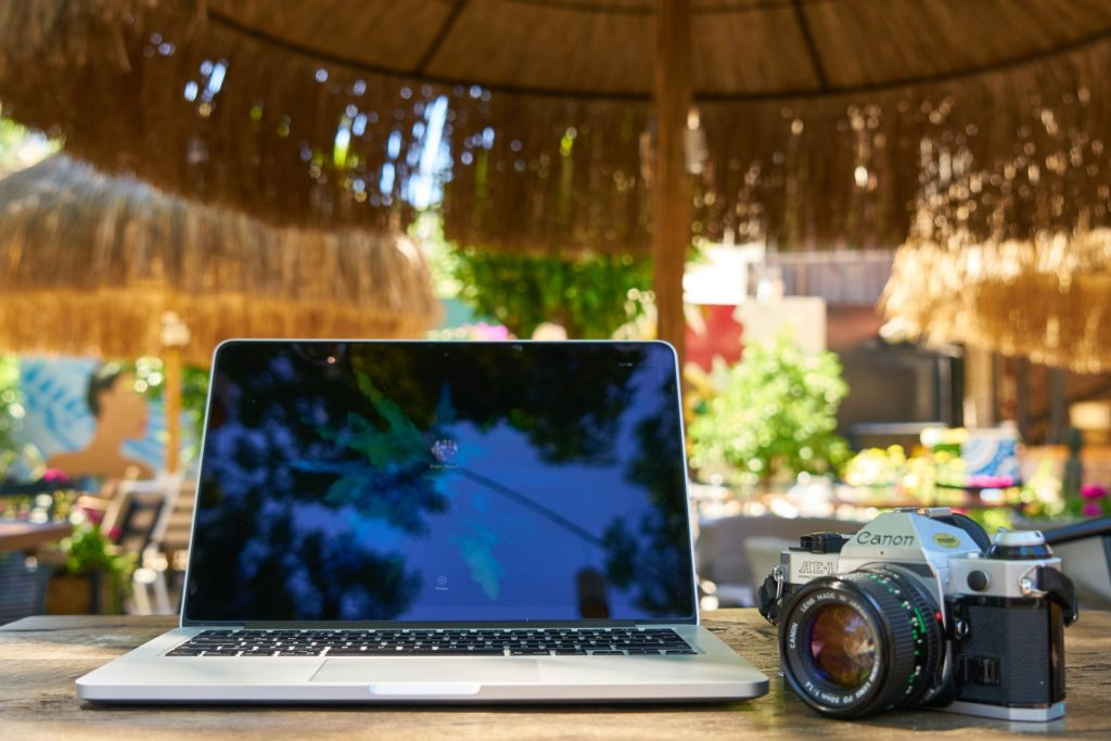 Computer and camera on travel. Remote work