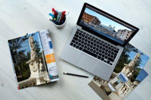 Travel Research with laptop, phone and guides