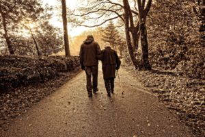 Man and woman who is blind are walking along a wooden trail.