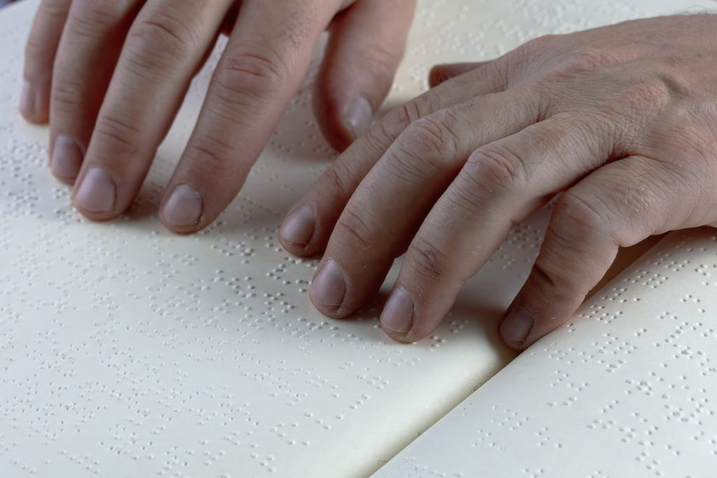 Hands reading a braille document.