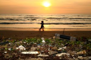 Runners on a beach covered with trash at sunset.
