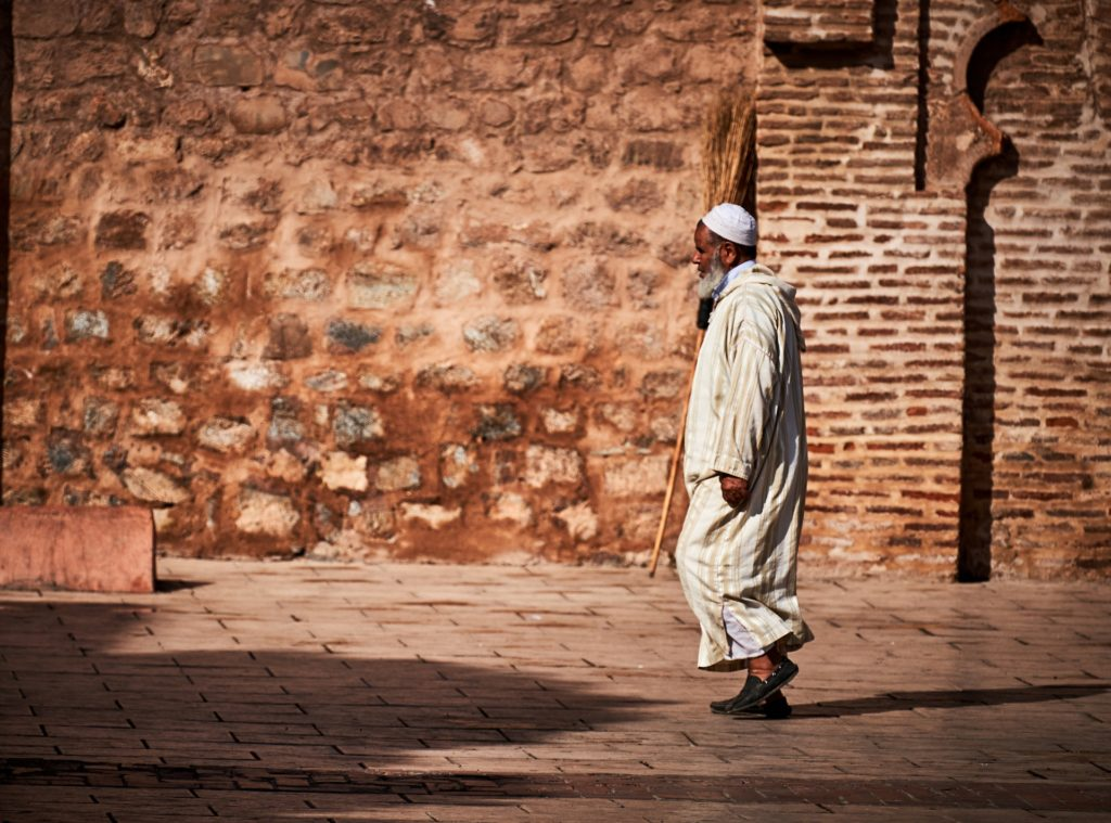 Man walking along the red walls in Marrakesh