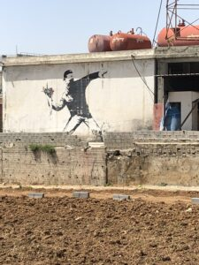 Artist painting of Palestinian throwing roses across West Bank