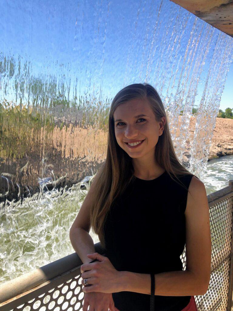 Breana Johnson standing behind a waterfall.